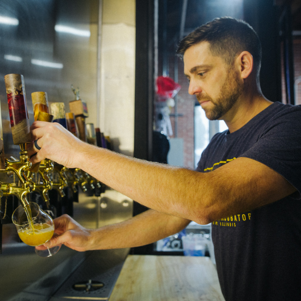 A man pulls a beer tap in a brewery