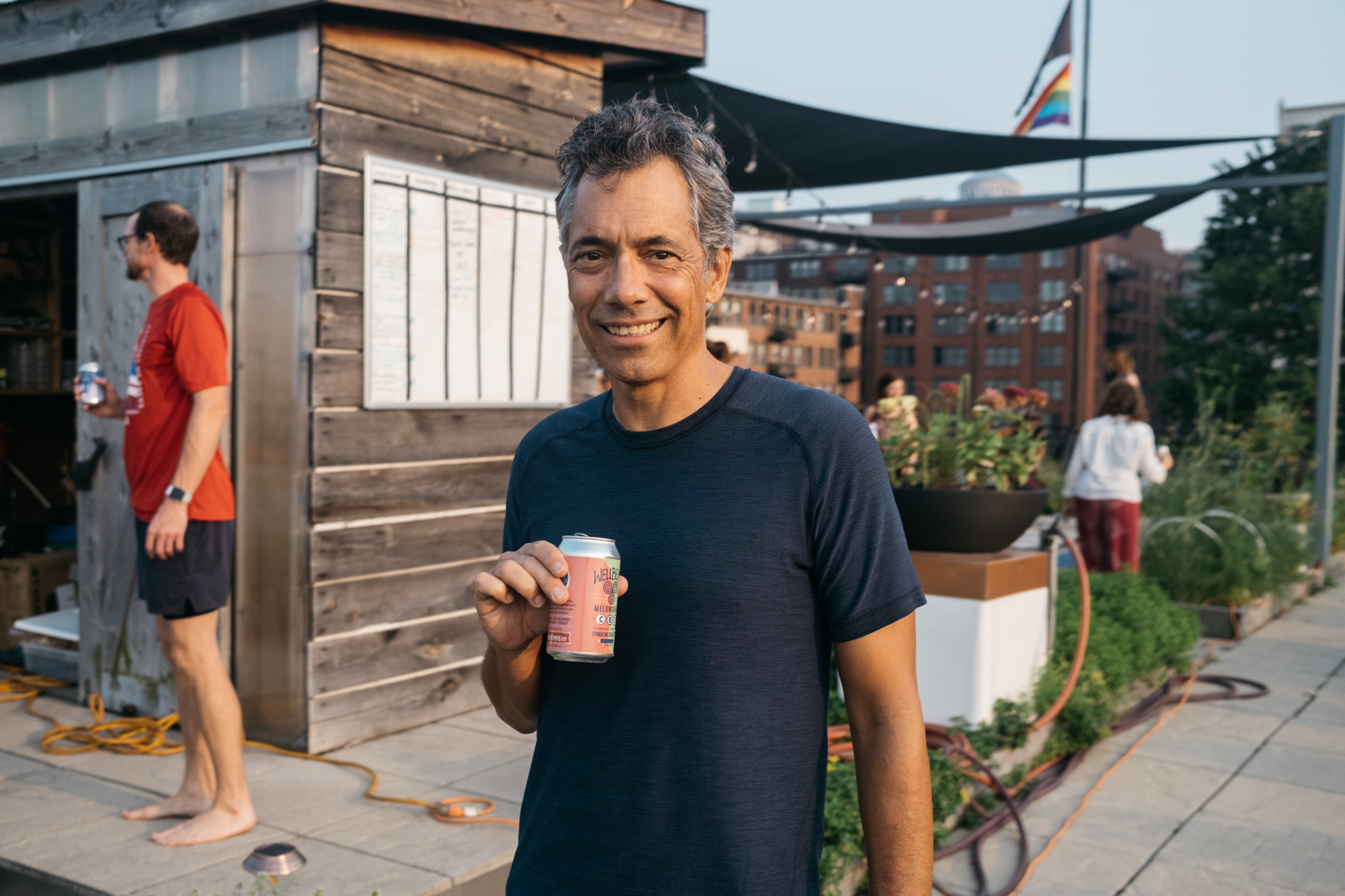 White man holding a beverage standing on a rooftop.